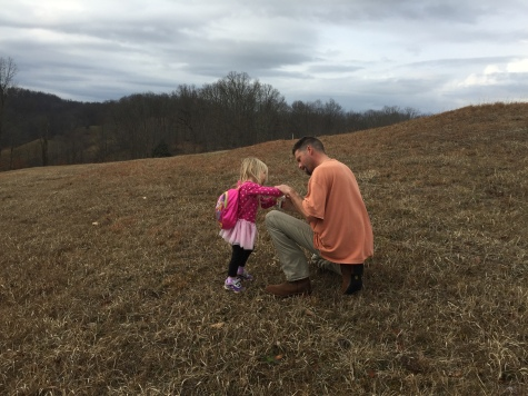 Daddy and daughter in the cow pasture--she got a prickle in her finger.